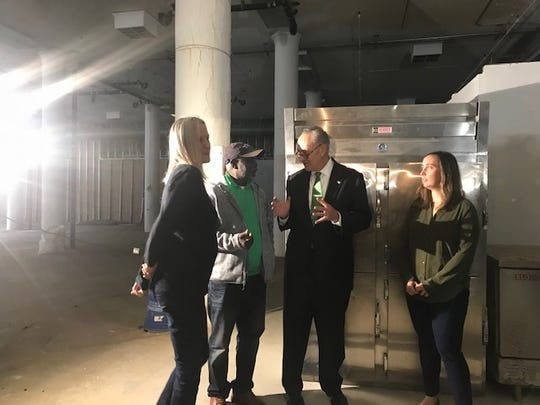 At a press conference, U. S. Senator Charles E. Schumer met with three entrepreneurs who are interested in working with The Commissary Downtown Kitchen Incubator. From left to right are Visna Clayton, Embola Ekille, Schumer and Brighid O'Keane.