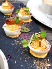 The deviled eggs have slivers of bacon and bright pops of pink from purple sauerkraut powder. Micro greens and rye bread crumbs garnish the plate.