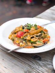 The farmers' hash features fingerling potatoes, carrots, corn, zucchini, cherry tomatoes and fresh herbs finished in a savory mushroom pan gravy .