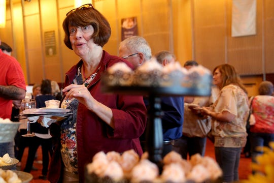 Nancy McPhail, of Aumsville, tries a cupcake from Sweetly Baked during the 20th annual Chef's Nite Out, a fundraiser benefiting the Marion-Polk Food Share, at the Salem Convention Center on Sunday, Oct. 14, 2018.