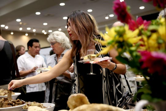 A woman grabs a sample from The Bread Board during the 20th annual Chef's Nite Out, a fundraiser benefiting the Marion-Polk Food Share, at the Salem Convention Center on Sunday, Oct. 14, 2018.