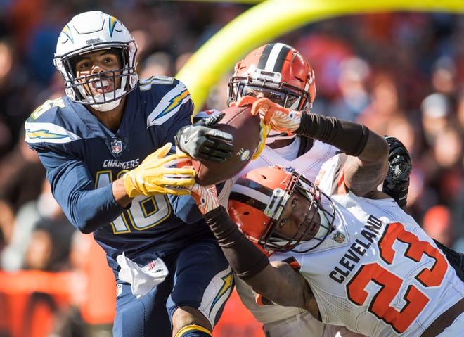 Oct 14, 2018; Cleveland, OH, USA; Los Angeles Chargers wide receiver Tyrell Williams (16) catches a touchdown as Cleveland Browns strong safety Damarious Randall (23) and defensive back Derrick Kindred (26) defend during the first half at FirstEnergy Stadium. Mandatory Credit: Ken Blaze-USA TODAY Sports