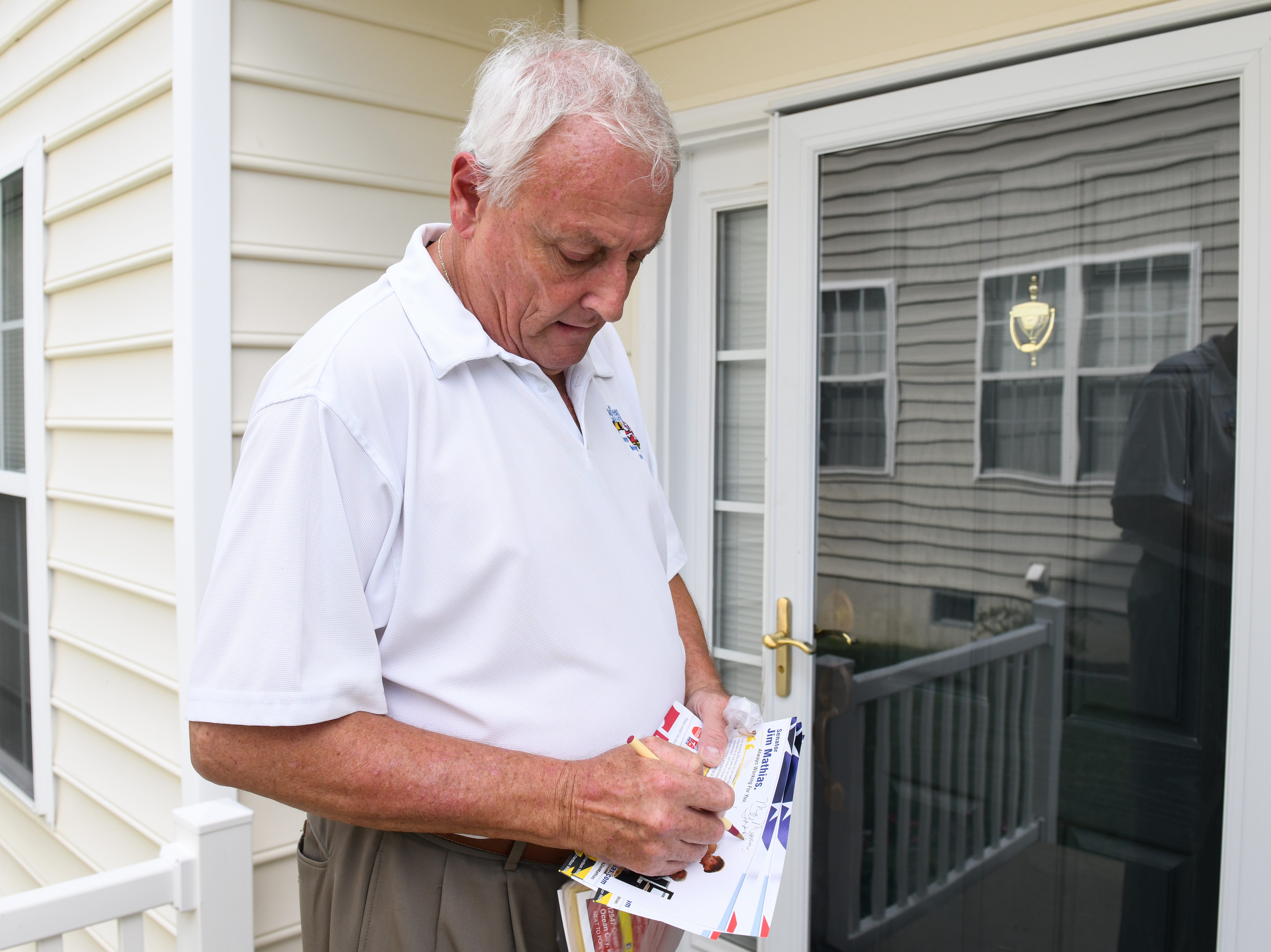 Sen. Jim Mathias, Democratic incumbent candidate for Maryland State Senate in District 38, leaves a note for a voter in Ocean Pines while campaigning on Tuesday, Oct 2, 2018.