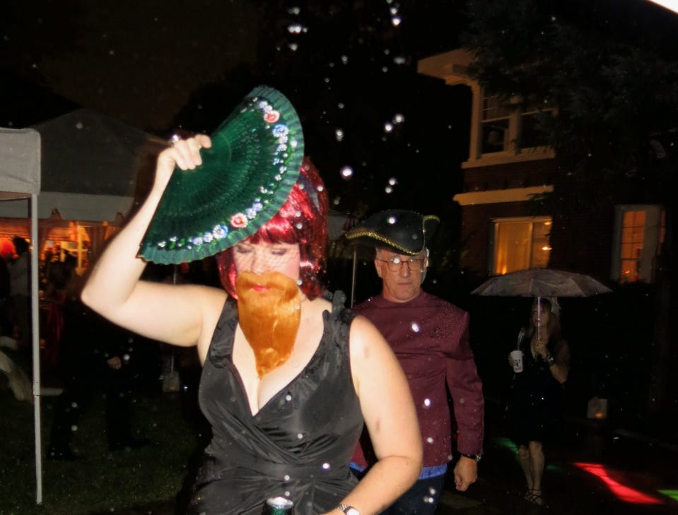 Amy Quinn makes a mad dash between raindrops during Krewe of Highland Coronation on Oct. 12.