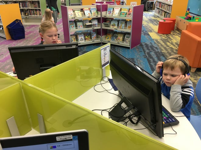 Katelyn Mueller, 7, and her brother Joshua Mueller, 5, play on the computers at the Caille Branch Library on Friday afternoon in Sioux Falls. The children have gone to the library on a regular basis for the last five years as a way to develop literacy skills and participate in free activities throughout the year.