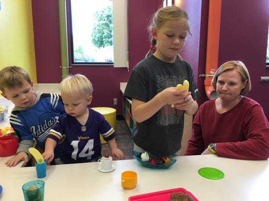 The Mueller family plays with toy kitchen supplies and food in the children's area of the Caille Branch Library  on Friday afternoon in Sioux Falls. The family has been visiting the branch for five years because of the ever-changing activities the site offers young children.