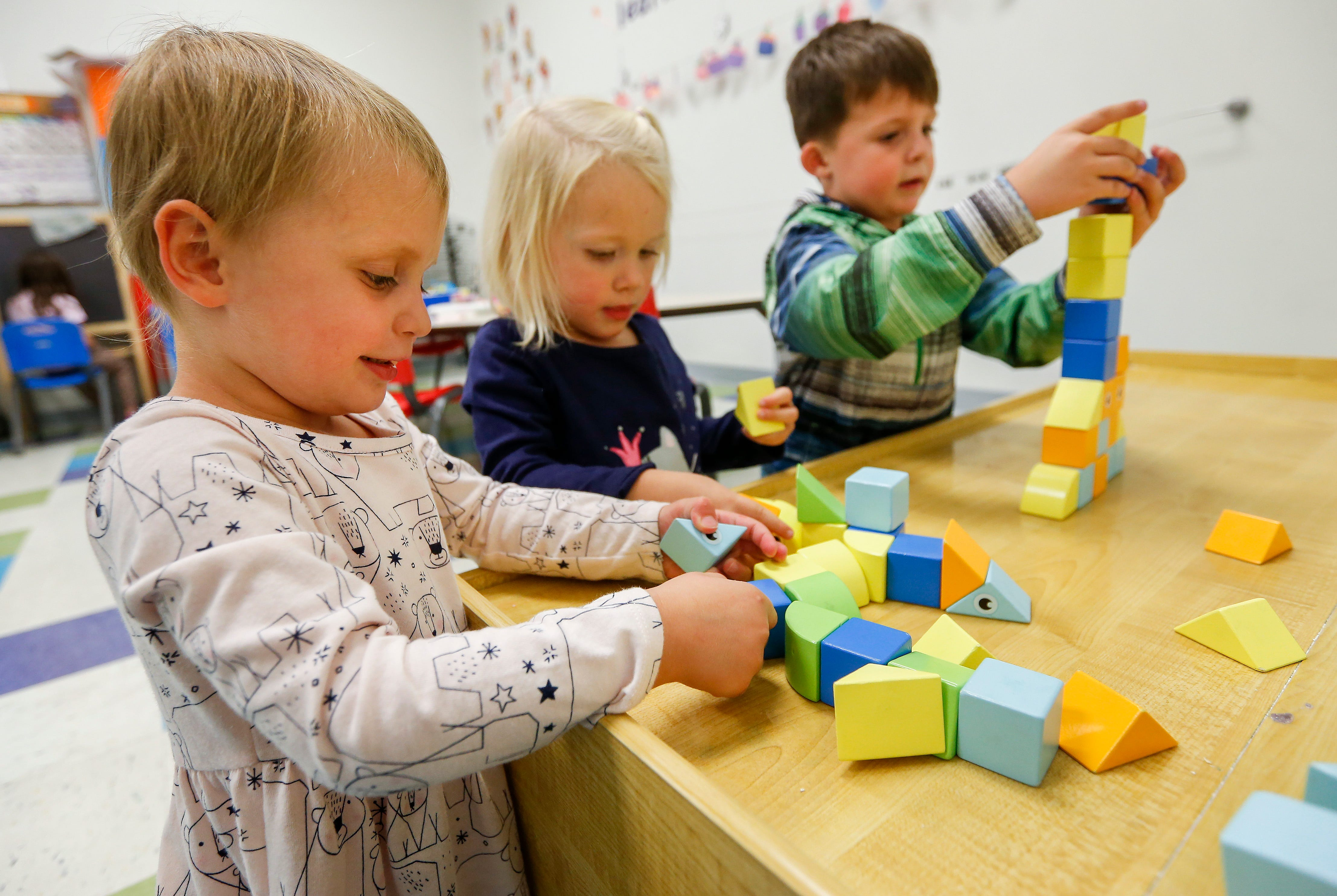 From left, Sutton Hamlet, 3, Amelia Shoemaker, 2, and Jamison Hamlet, 4, play with magnetic wooden blocks that were created by Craig and Fawn Rechkemmer, owners of Itty Bitty City.