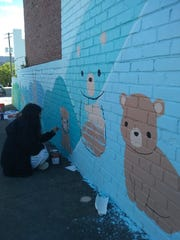 Artist Julia Chon painting a mural on Oct. 13, 2018 in Waynesboro for the Virginia Street Art Festival.