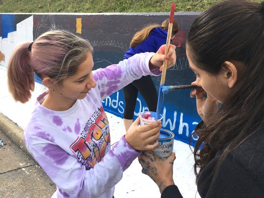 Heather Godwin, left, and Courtney Begoon were two of the Fort Defiance freshmen helping paint the school's spirit wall this past weekend.