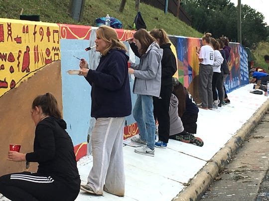 Students and staff of Fort Defiance High School help paint the school's spirit wall Sunday afternoon.