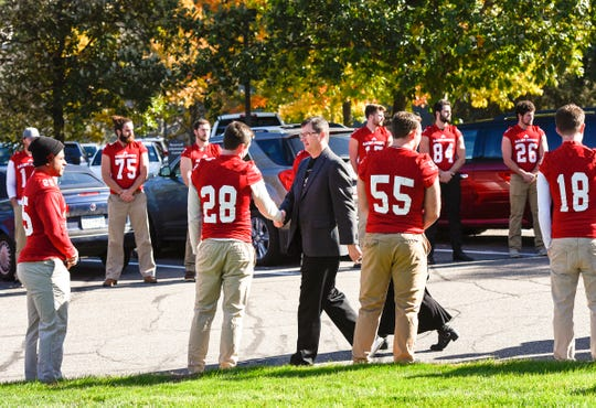 Jim Gagliardi, son of long time St. John's University football coach John Gagliardi, shakes hands with the football players at his fathers funeral Monday, Oct. 15, at the St. John's Abbey in Collegeville.