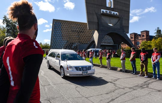 St. John's University Football players line the road as long time St. John's University football coach John Gagliardi passes in a hearse Monday, Oct. 15, at the St. John's Abbey in Collegeville.