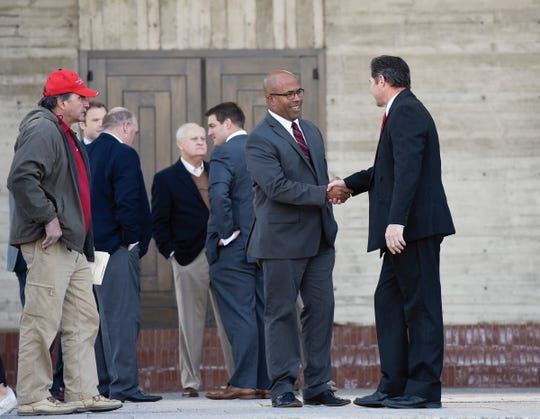 Former St. John's University football player Brett Mushatt shakes hands with SJU coach Gary Fasching after the funeral of long time coach John Gagliardi Monday, Oct. 15, at the St. John's Abbey in Collegeville.
