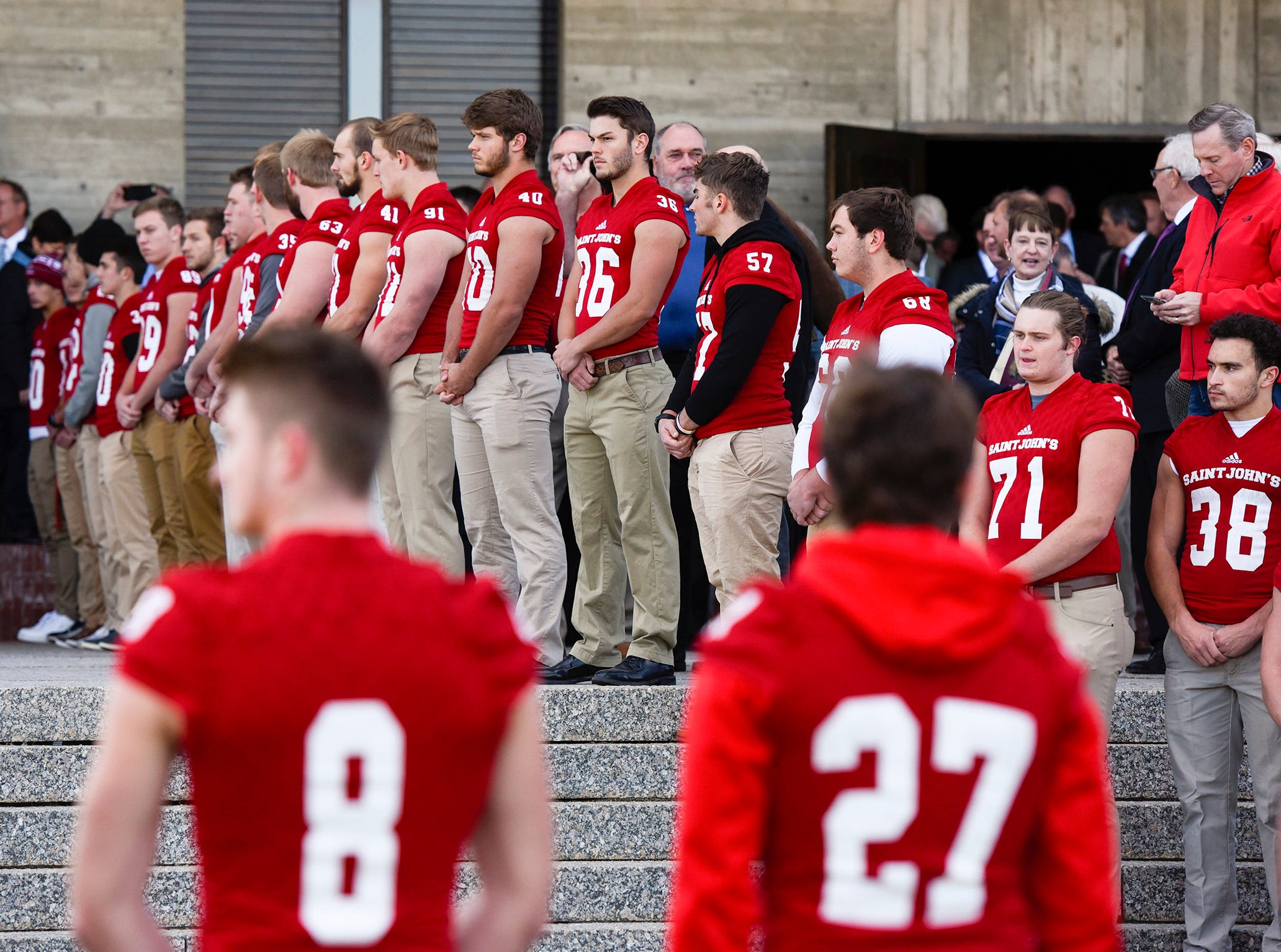 St. John's University Football players stand solemnly as the casket of long time St. John's University football coach John Gagliardi is carries to a hearse Monday, Oct. 15, at the St. John's Abbey in Collegeville.