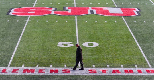Former St. John's University football player Chuck Williams, Minneapolis, and 1982 graduate, walks across the football field alone before the funeral of his coach John Gagliardi Monday, Oct. 15, at the St. John's Abbey in Collegeville.