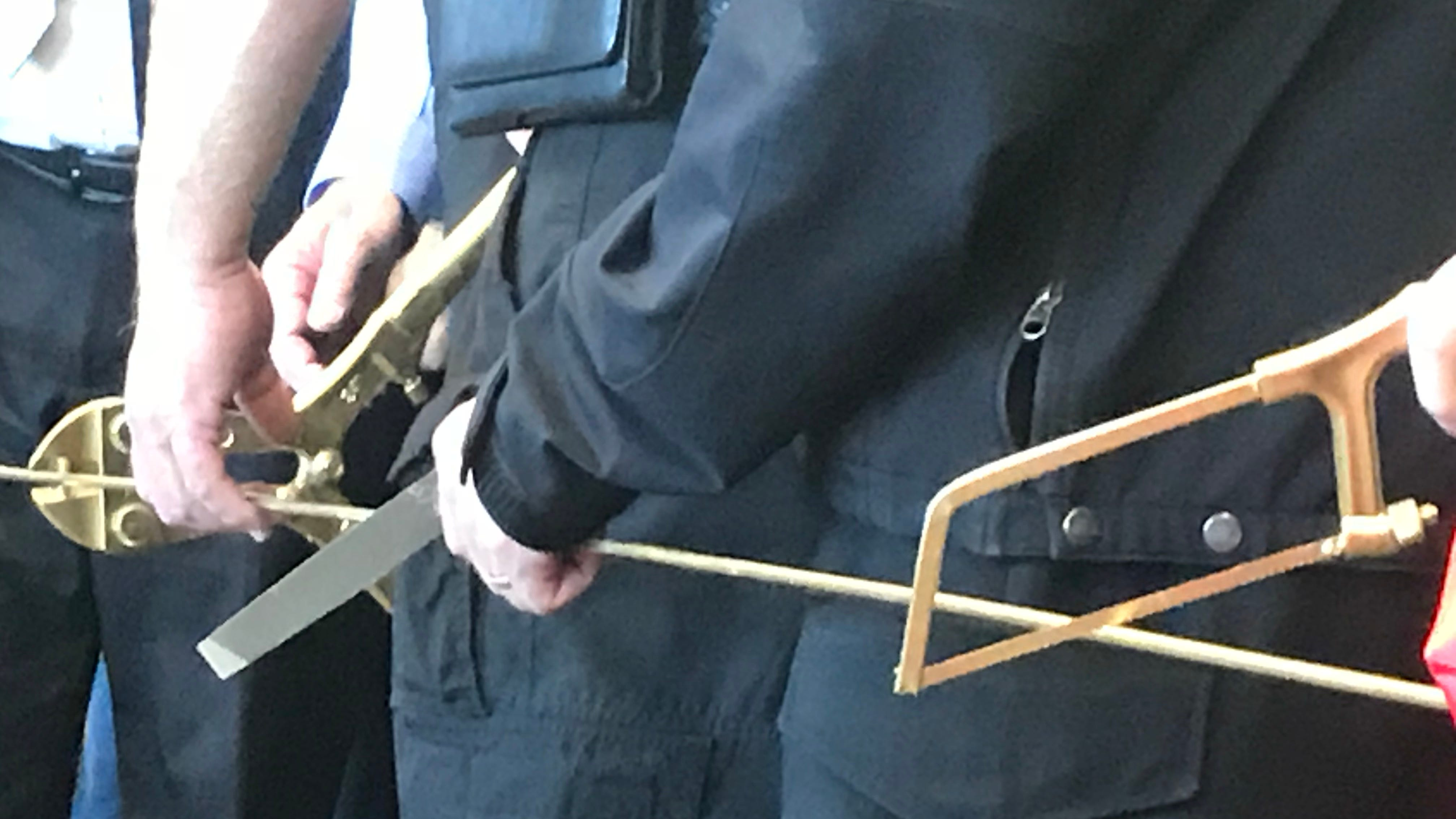 """Washington County Sheriff's Office personnel joined other county officials Monday in celebrating the opening of a new expansion at Purgatory Correctional Facility that will house low-risk inmates who participate in a special work program.  A little jailhouse humor was involved, as they used bolt cutters, a file and a hacksaw, all spray-painted gold, for the """"ribbon cutting."""""""