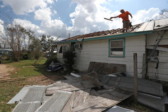 Bradly Jones works to repair the roof of the home in Sneads, Fla. that he shares with his wife Sherry Brady on Monday after Hurricane Michael ripped through the area earlier this week.
