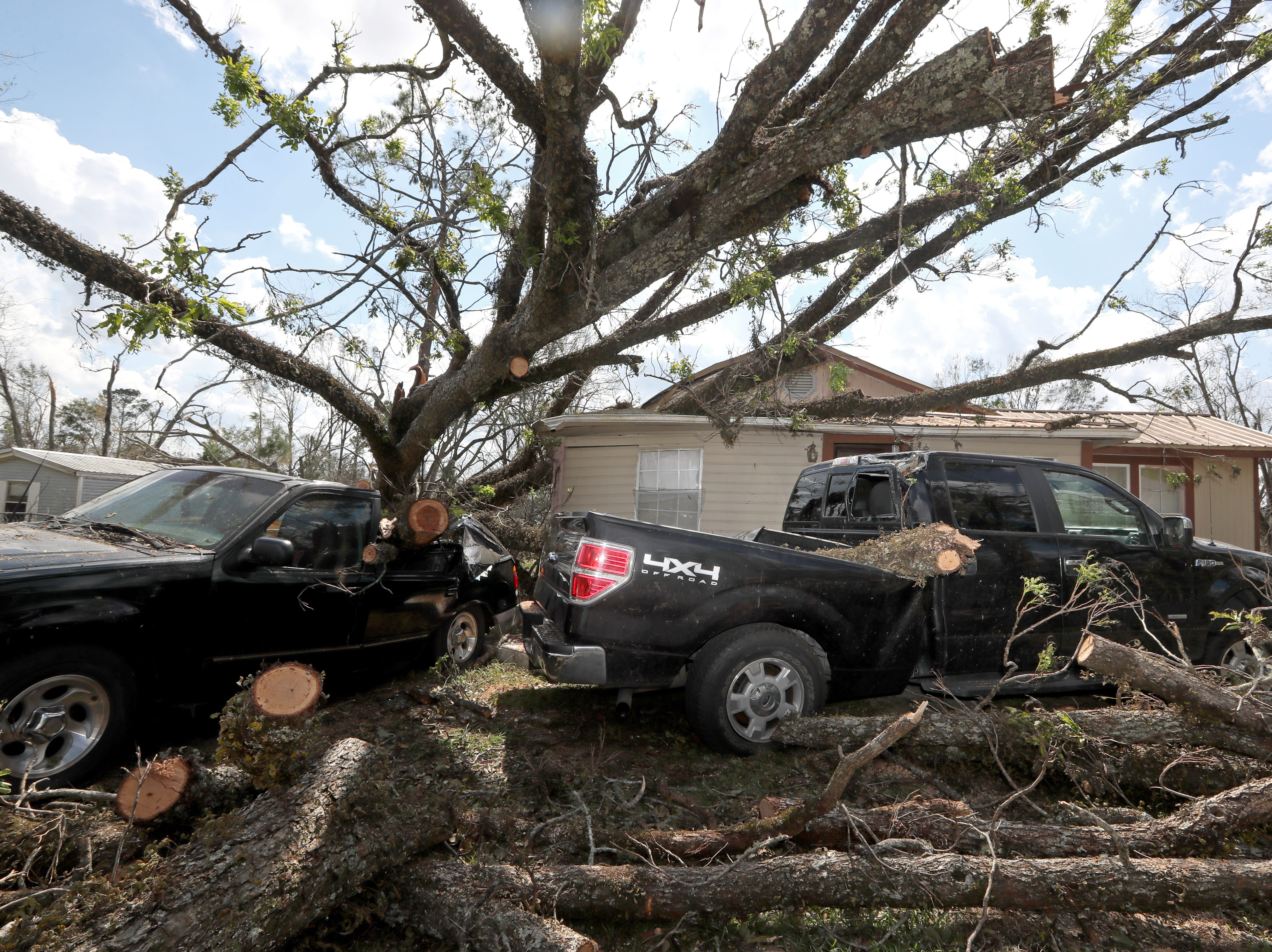 Carolyn Ortega's two Ford trucks are left smashed outside the front of her home in Sneads, Fla. where she waited out Hurricane Michael with her family.