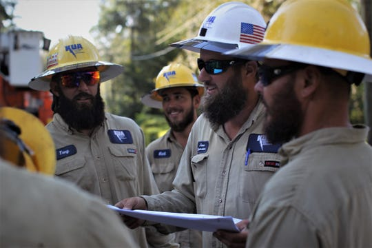 Foreman Jason Wright talks to his Kissimmee Utility Authority crew about where to go next in Tallahassee's Indian Head Acres to repair power line damage from Hurricane Michael.