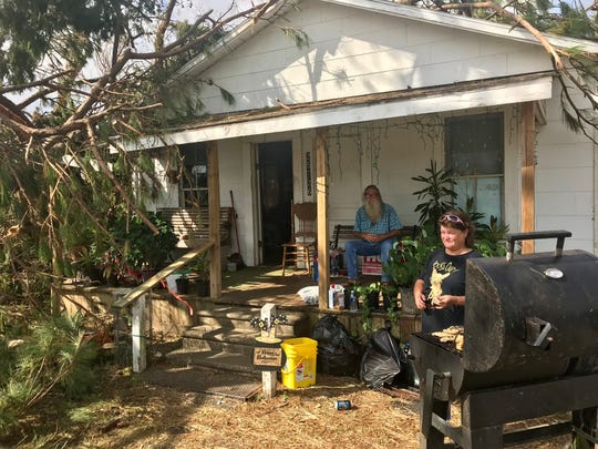 Patricia Wallace grills catfish, chicken and rabbit outside her hurricane-damaged home Monday in Altha as her husband John Wallace sits on the porch.