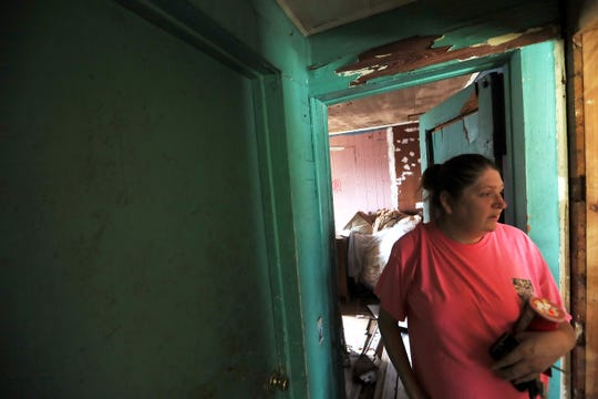 Sherry Brady walks through her Sneads, Fla. home Monday as her husband Bradly Jones works to cover the home with a tarp, after Hurricane Michael tore the roof of their house.