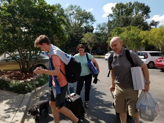 """John and Lisa Richardson, along with their son Tanner and dog """"Clifford,"""" evacuated from Panama City to Orlando. They checked into the Hilton Garden Inn off Thomasville Road."""