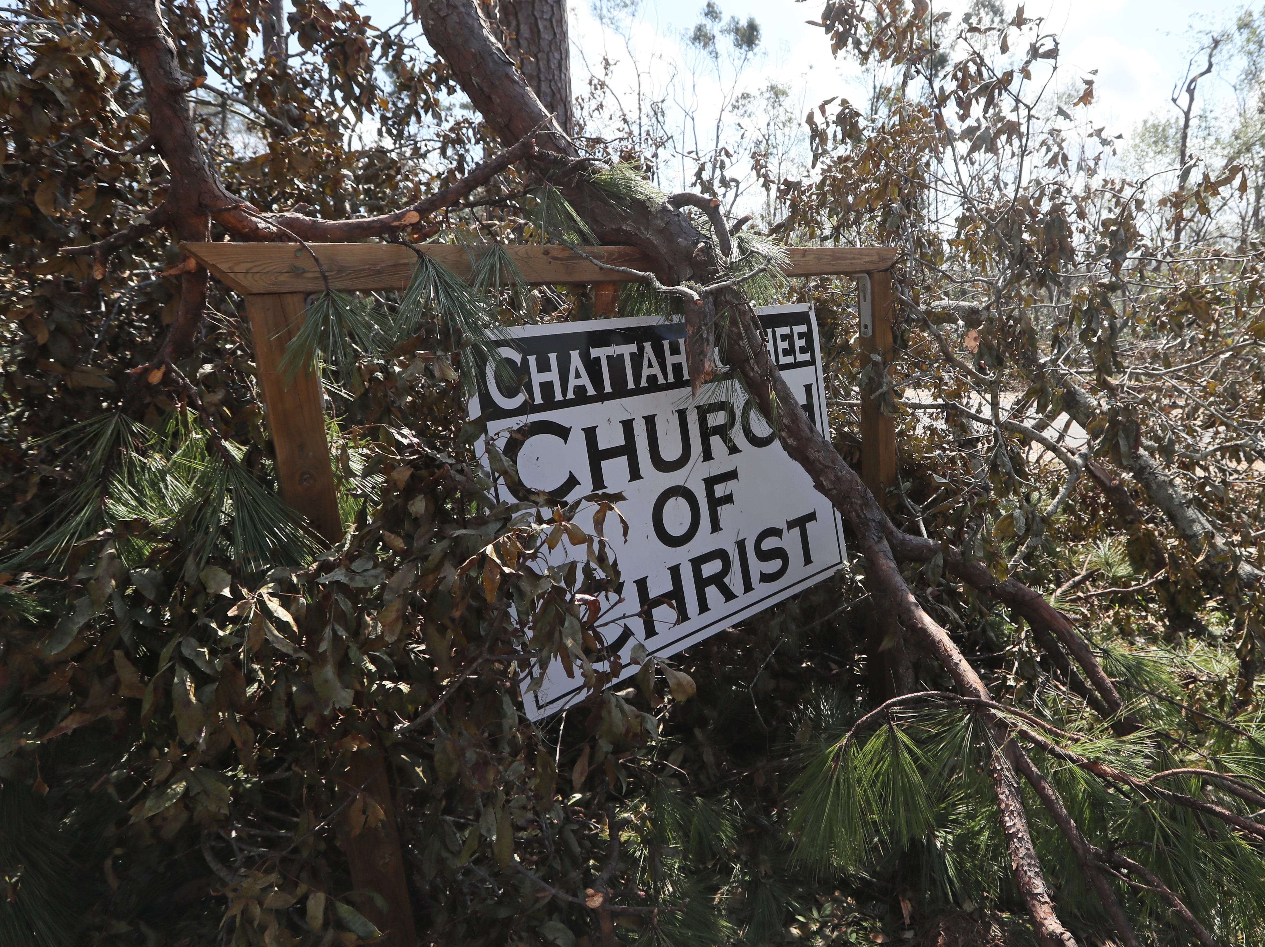 Fallen trees cover the signage of the Chattahoochee Church of Christ along Hurricane Michael's path Monday, Oct. 15, 2018.