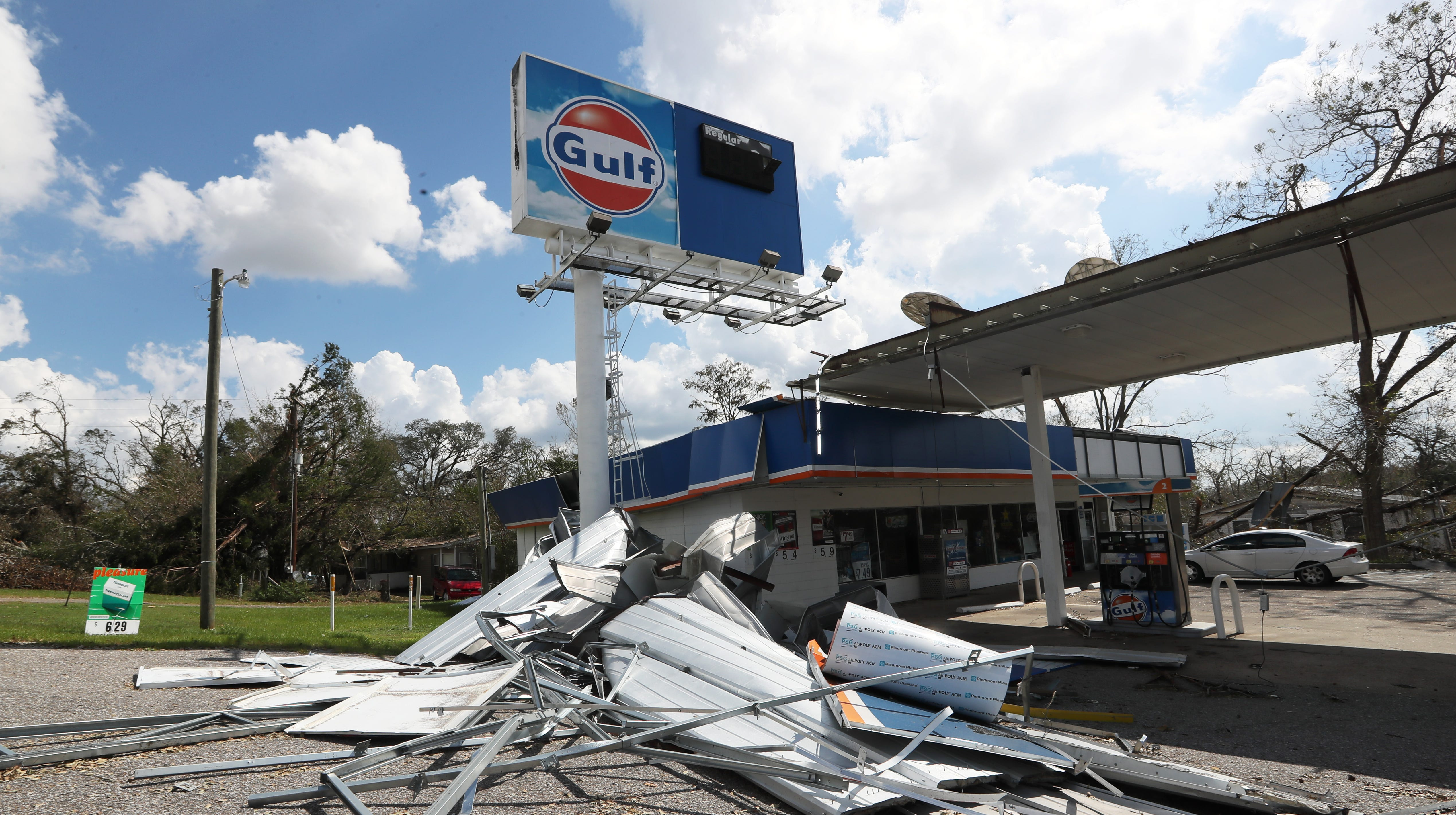 The roof of a gas station's awning is left in ruin along the roadside of Highway 90 in Sneads, Fla. after Hurricane Michael swept through town.