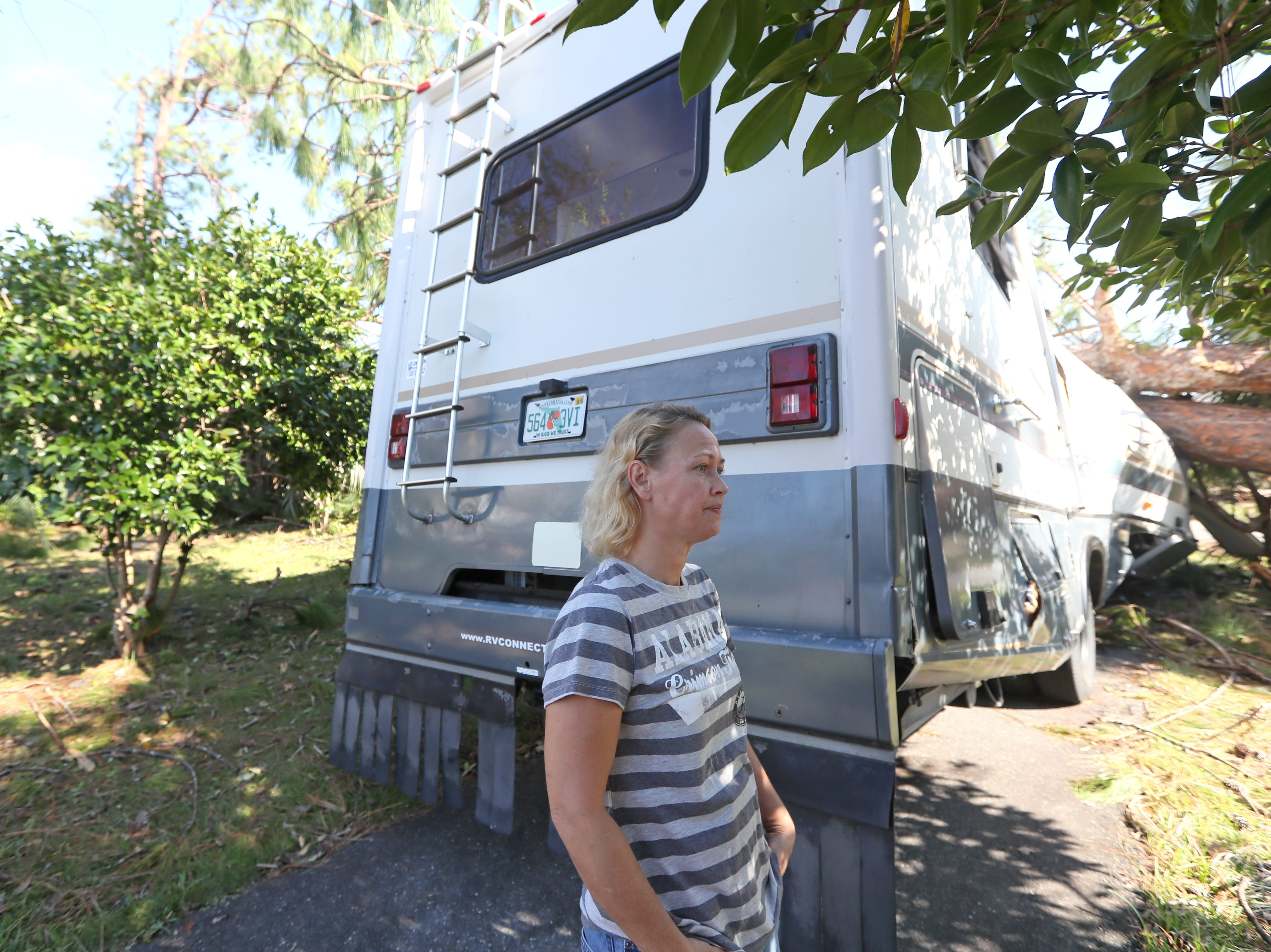 Tammy Patrick stands outside of her RV after it was crushed by a fallen tree from Hurricane Michael's path in Chattahoochee, Fla. Monday, Oct. 15, 2018.