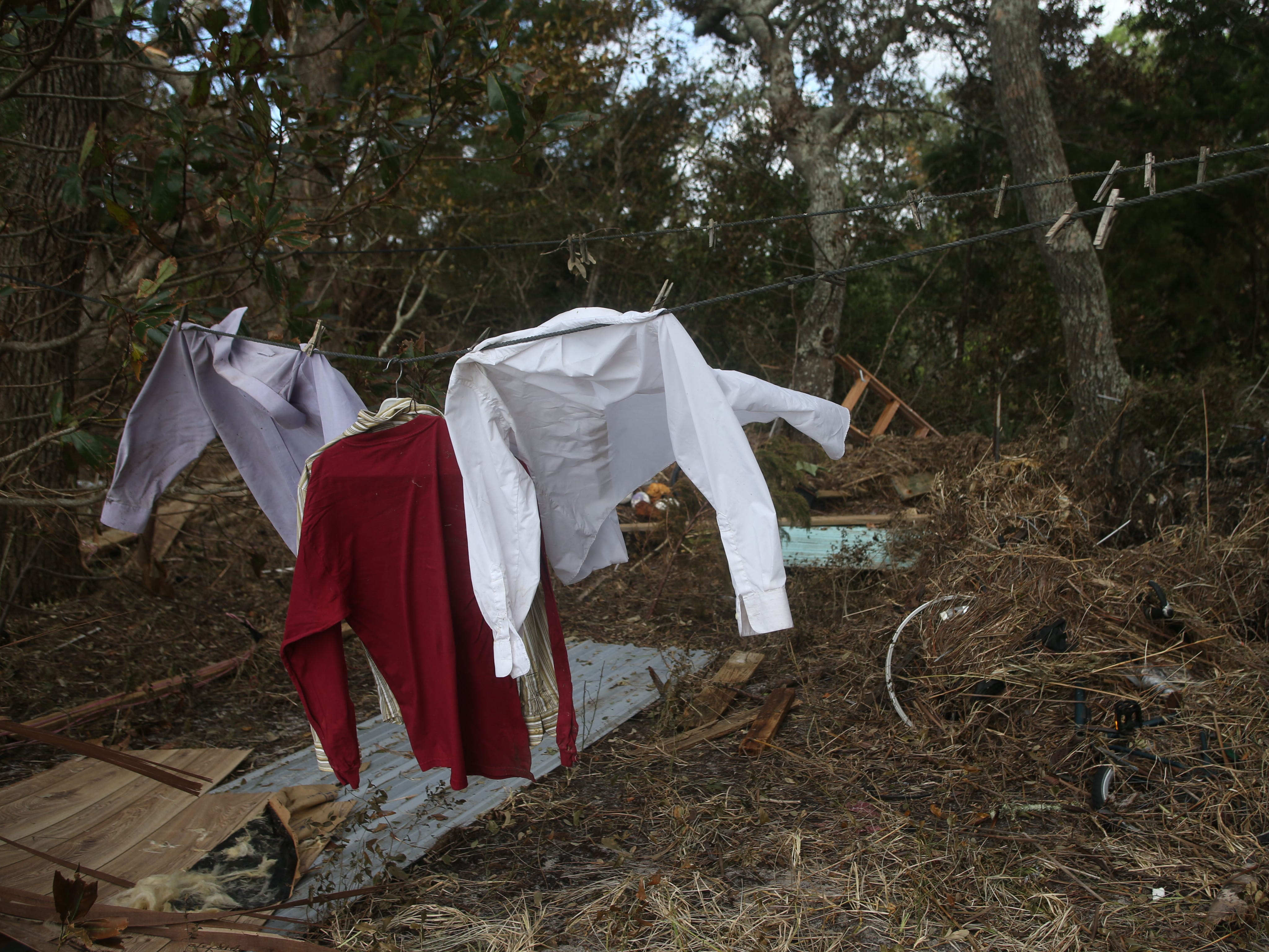 A clothesline swings in the wind and debris litters the ground in Lanark, Fla. after Hurricane Michael on Monday, Oct. 15, 2018.