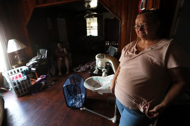 Carolyn Ortega, 53, begins to tear up Monday as she recalls the afternoon spent with her eight family members in her Sneads, Fla. living room, while Hurricane Michael brought trees crashing down all around the house.