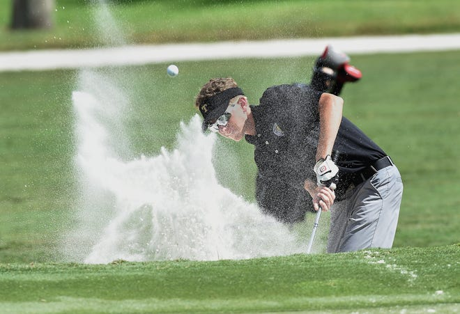 Jackson Harris, of Treasure Coast High School chips out of a bunker onto the 11th green during the boys golf district 17-3A tournament at The Florida Club on Monday, Oct. 15, 2018, in Martin County.