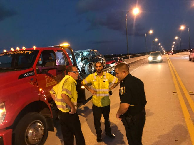 Martin County Sheriff's Deputy Jacob Blaszyk confers Sunday with tow truck operators about a three car collission on Northeast Causeway Boulevard in Jensen Beach.