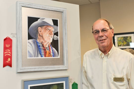 "Backus Art Museum Board of Directors member Karl Guettler with second place watercolor,  ""I Willie Love You"" by Colleen Nash Becht."