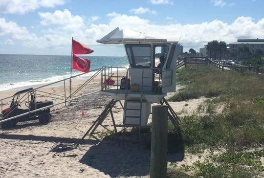 Double red flags fly Monday, Oct. 15, 2018, at Conn Beach in Vero Beach to warn beachgoers about possible red tide in the ocean water.