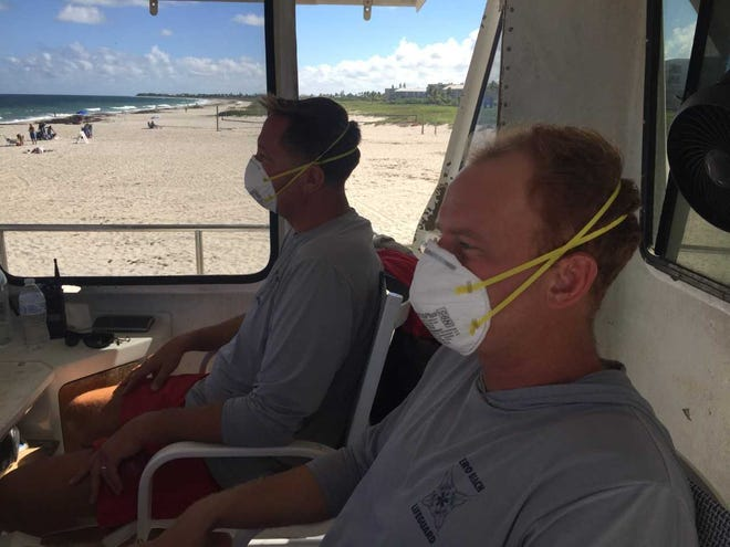 Vero Beach lifeguards Erik Toomoo, left, and Colter Hanawalt wear face masks in case of red tide in the air Monday, Oct. 15, 2018, while watching over South Beach.