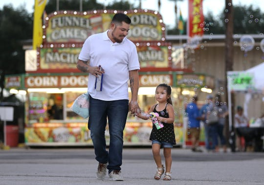 Luis Mireles, a resident of Rosenberg, Texas, walks through the Fort Bend County Fair with his daughter. Mireles cited his father and wife being immigrants as his reason for choosing Beto O'Rourke for Senate over incumbent Ted Cruz.