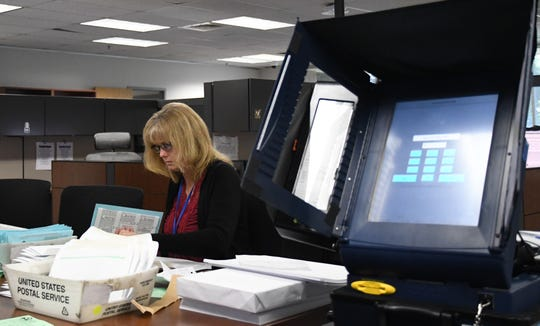 Vote by mail clerk Maryalice Cypert prepares ballots beside the election office's voting machine.