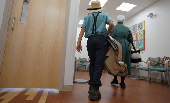 An Amish boy carries his brother in a baby carrier with his mother alongside as they leave the Nemours Kinder Clinic in Dover that treats the Amish community.