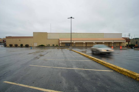 A car drives past the former Sears in Prices Corner that has been closed since last spring. Sears filed for Chapter 11 bankruptcy protection and will close another 142 stores by about the end of the year, on top of a recently announced round of 46 store closures, as part of the bankruptcy.