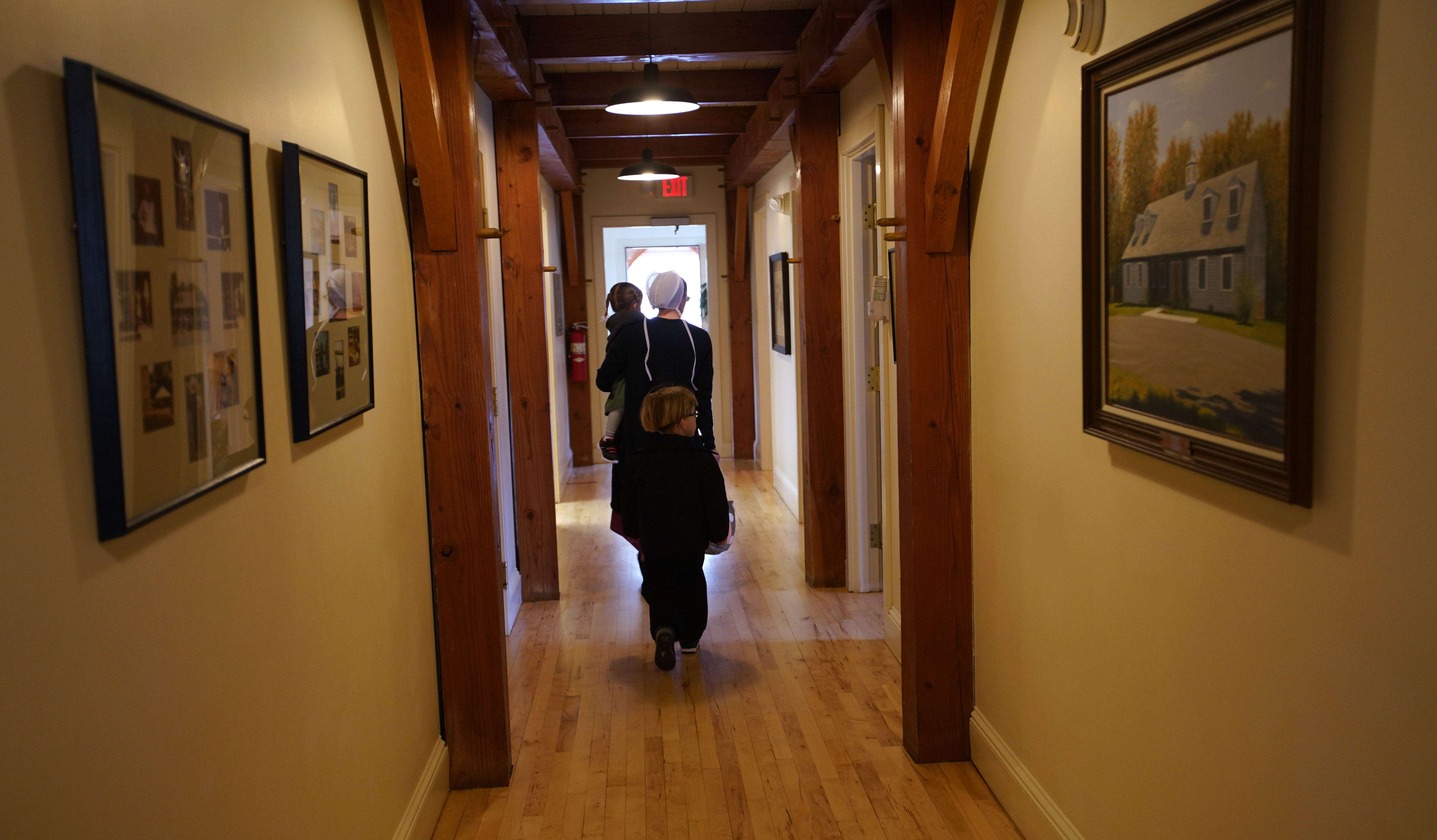 An Amish mother and her two young children walk through a hallway in the Clinic for Special Children in Strasburg, Pennsylvania.