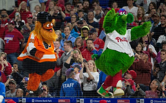FILE - In this Sept. 29, 2018, file photo, Gritty, the Philadelphia Flyers' mascot, left, and the Philly Phanatic dance during a baseball game between the Philadelphia Phillies and the Atlanta Braves, in Philadelphia.
