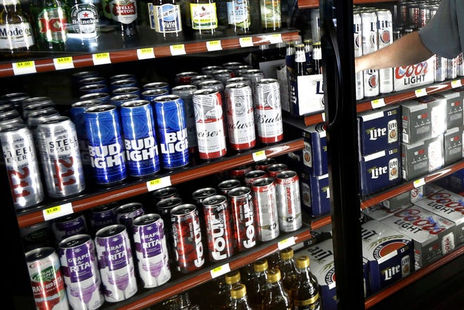 """FILE - This Wednesday, April 19, 2017 file photo shows the beer cooler behind the counter in a convenience store in Sheridan, Ind. In future sweltering years with a double whammy of heat and drought, losses of barley yield can be as much as 17 percent, computer simulations show. And that means """"beer prices would, on average, double,"""" even adjusting for inflation, said a study published in the journal Nature Plants on Wednesday, Oct. 17, 2018."""