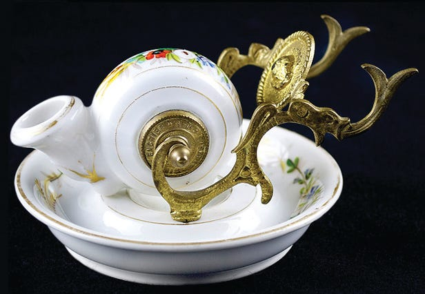 "This ""snail,"" an antique inkwell form, was made around 1860. It is porcelain with painted flowers as decoration. A collector paid $156 for it at a New Jersey auction."