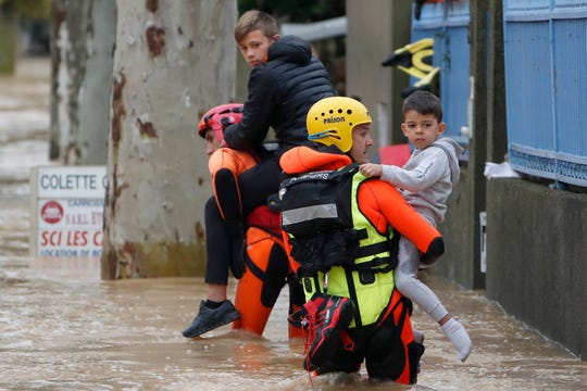 French firefighters carry children during rescue operations in the middle of submerged streets in Trebes, France, Oct. 15, 2018.