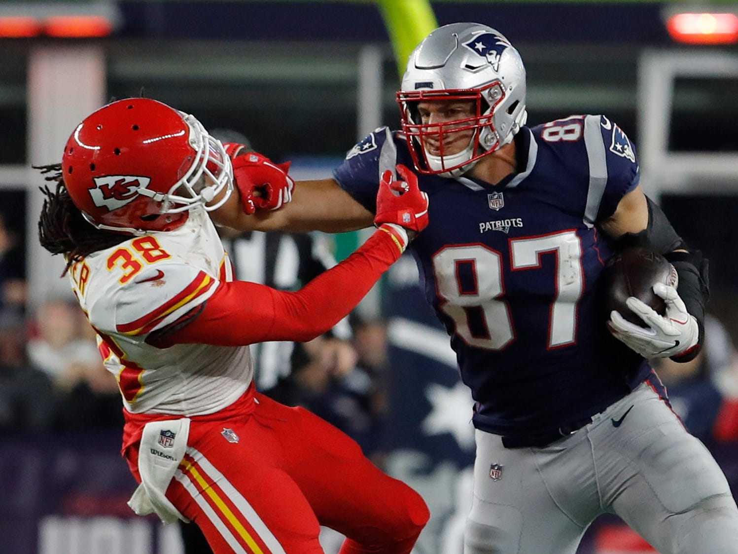 Patriots tight end Rob Gronkowski makes a catch and stiff arms Kansas City Chiefs free safety Ron Parker in the second half at Gillette Stadium.