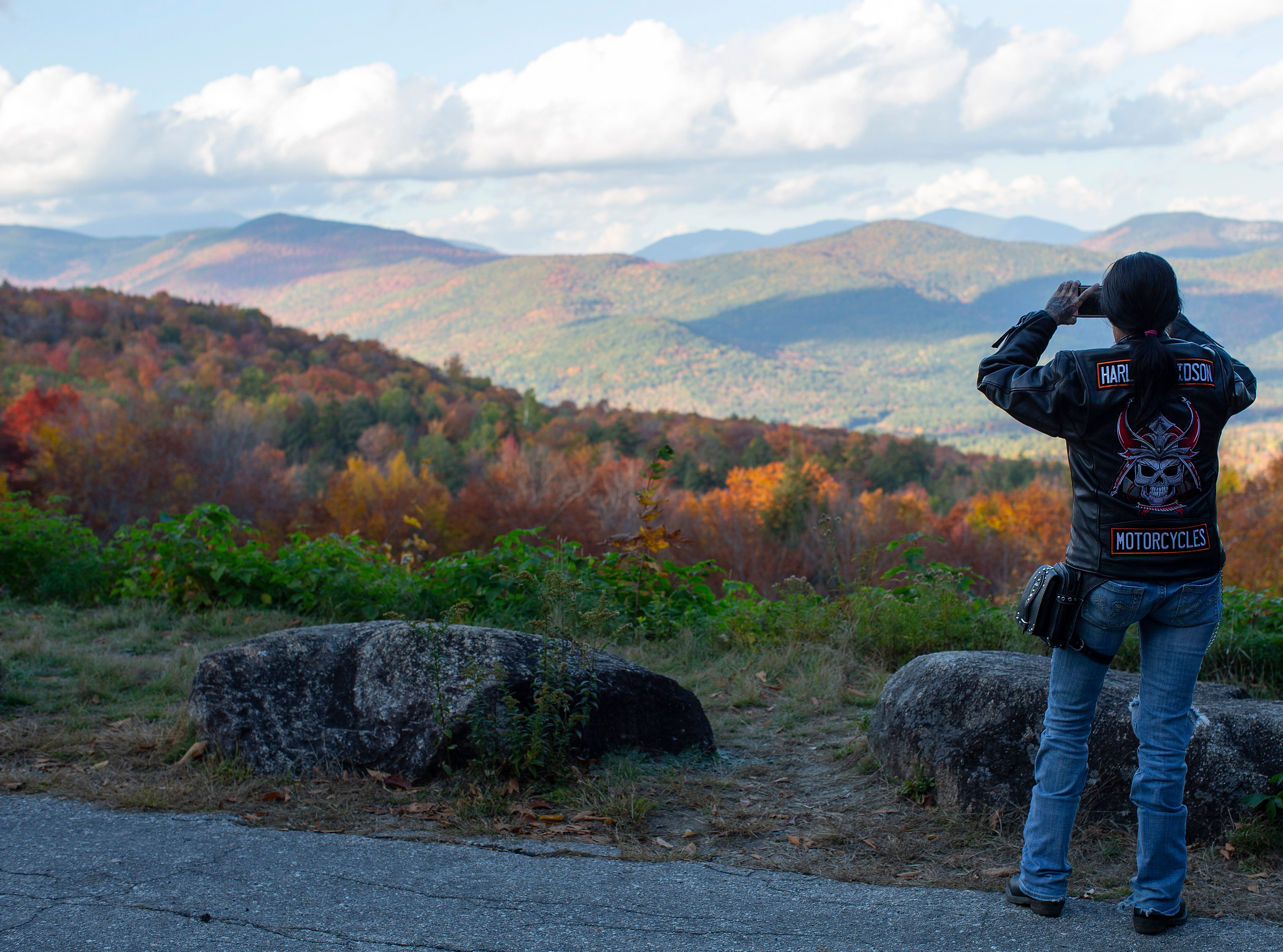 A woman photographs the fall foliage colors along the Kancamangus Highway in Bartlett, N.H. on Oct. 10, 2018.