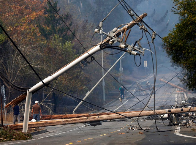 In this Tuesday, Oct. 10, 2017 file photo, people walk past a fallen transformer and downed power lines in Santa Rosa, Calif. California fire officials say sagging Pacific Gas and Electric power lines that made contact ignited a blaze last year in California that killed four people and injured a firefighter.