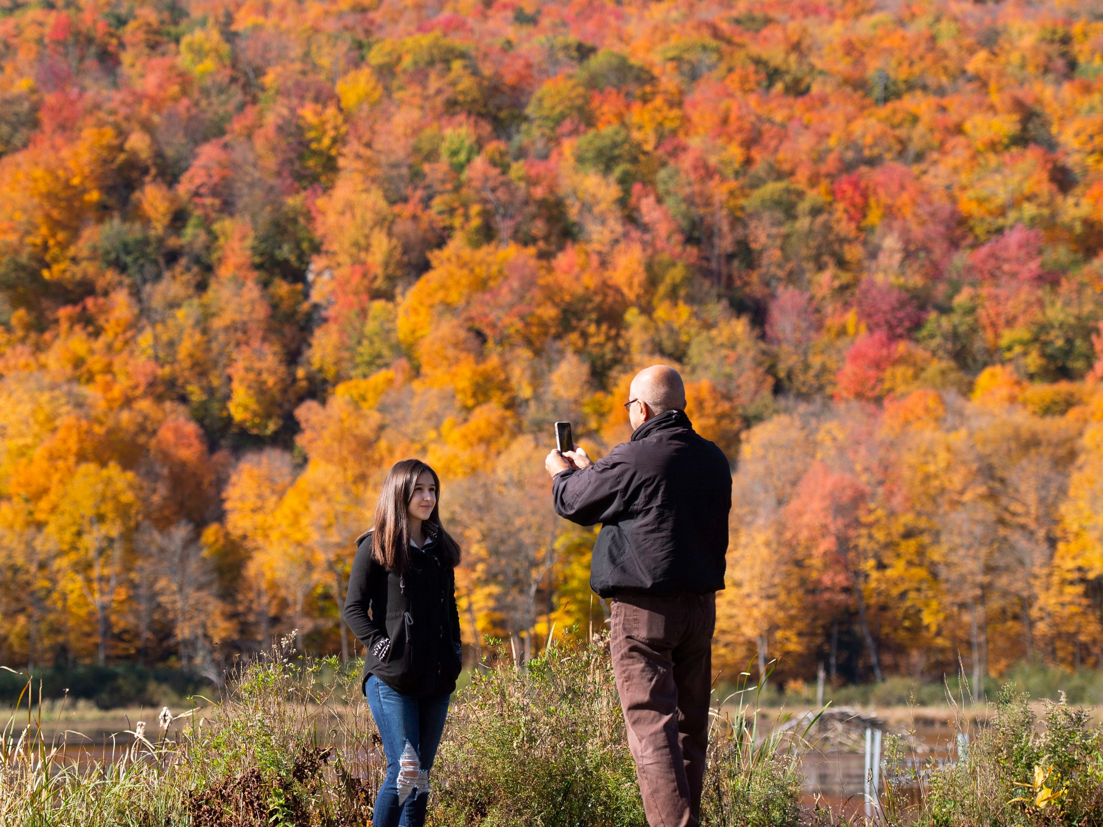 Essie Khossravi takes a photo of his daughter Nika, 14, as they take in the fall colors in Gatineau Park in Chelsea, Quebec, on Sunday, Oct. 14, 2018.