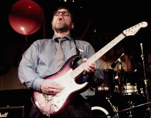 Microsoft co-founder and billionaire Paul Allen joins in with the band and electric guitar at an election night victory party in the early morning hours June 18,1997, in Seattle.